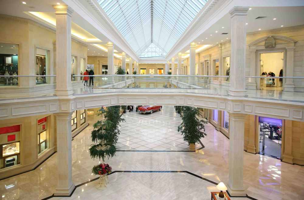 white and cream marble shopping mall with a red car in the background