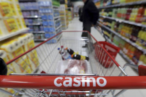 A customer stands in an aisle near a shopping trolley in a Casino supermarket in Nice